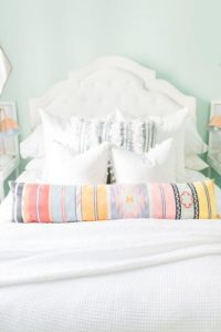 Provide guests with an assortment of pillows to help them sleep well. Image: Glitter Guide