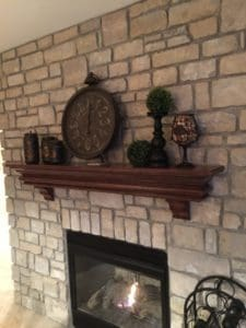 Draw attention to a clock on a mantel with other home decor items.